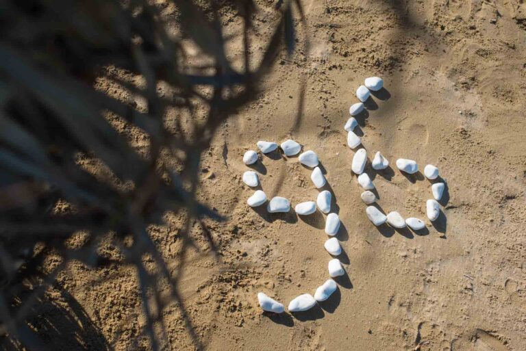 White pebbles, shaped as the number 96, on the golden sand of the gold beach in Paros.