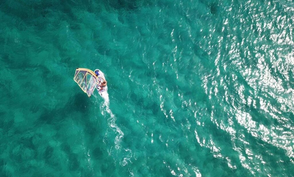 Top view of a wind surfer splashing through the bright blue sea at the golden beach in Paros.
